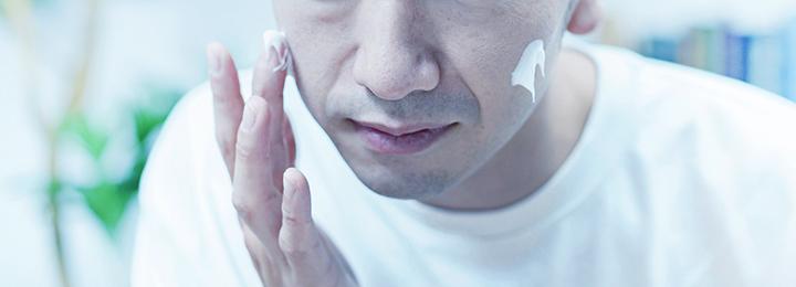 顔にクリームを塗る男性